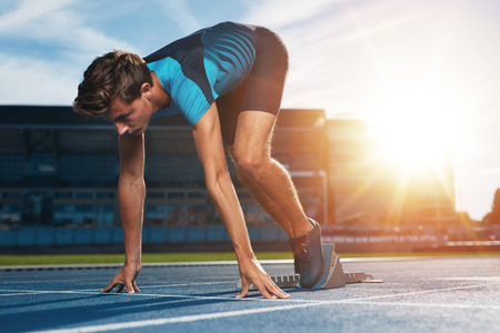runners: Young male runner taking ready to start position against bright sunlight. Sprinter on starting block of a racetrack in athletics stadium. Stock Photo