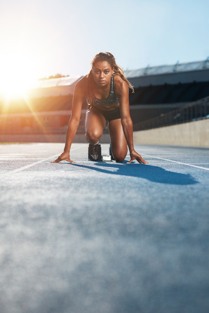 race start: Vertical shot of young female sprinter taking ready to start position facing the camera.  Woman athlete in starting blocks with sun flare. Stock Photo