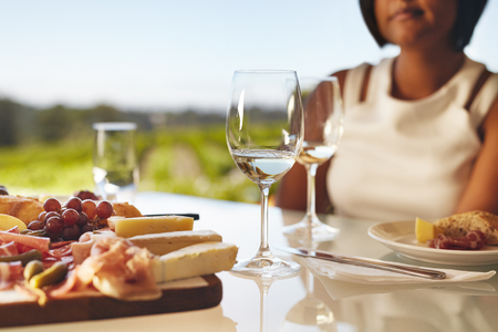 vineyard: Table set in the winery with two glasses of wine, cheese and grapes. Woman sitting in back at winery restaurant table.