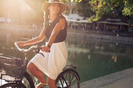 夏の日の池の近くの通りを自転車に乗って美しい若い女性の肖像画。サイクリングしながらよそ見帽子身に着けている女性。