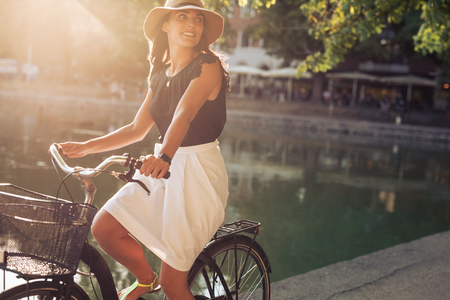 Portrait of beautiful young woman riding a bicycle along a street near pond on a summer day. Female wearing hat looking away while cycling. Stock Photo