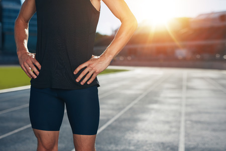 Mid section shot of male athlete standing on race track with his hands on hips on a bright sunlight. Cropped shot of young man runner on athletics running track in stadium.