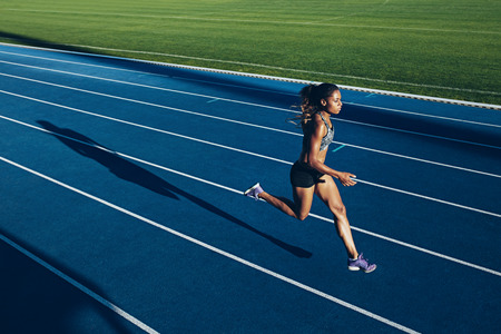Outdoor shot of young African woman athlete running on racetrack. Professional sportswoman during running training session.