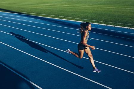 tir en plein air de jeune femme athlète africaine courir sur circuit. sportive professionnelle pendant la course session de formation.