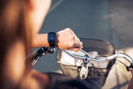 Hand of a woman with smartwatch. Close up shot of female on bicycle checking time on her smart wristwatch.