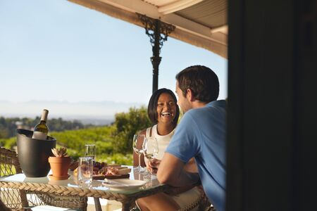wineries: Young couple on vacation drinking wine in a restaurant in countryside. Smiling young woman with her boyfriend in a winery restaurant.
