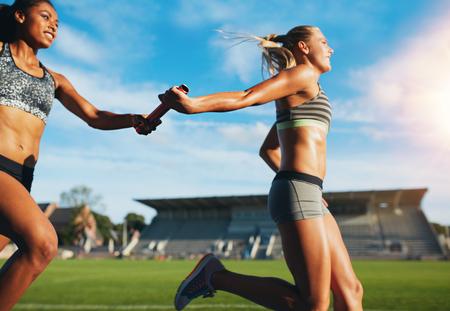 Weibliche Athleten, die über das Taktstock, während auf der Strecke. Junge Frauen laufen Staffellauf, Leichtathletikveranstaltung.