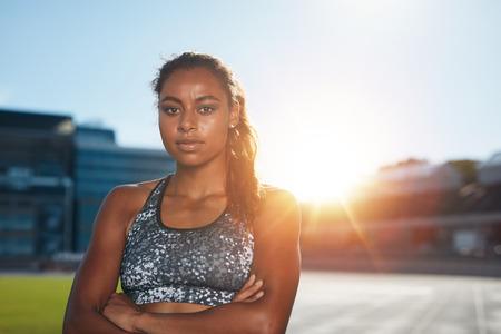 and athlete: Retrato de deportista joven conf�a en pie con las manos cruzadas sobre el estadio de atletismo que mira la c�mara con la luz del sol por detr�s. Atleta femenina africana en pista de carreras. Foto de archivo