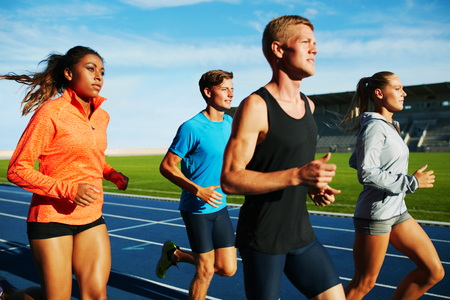 Group of multiracial professional athletes practicing running in stadium. Male and female athletes running together on racetrack.