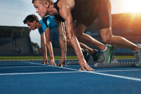 deportista: Dos jóvenes atletas en posición listo para iniciar una carrera de comenzar. Velocistas listo para la carrera en la pista de carreras con la flama del sol.