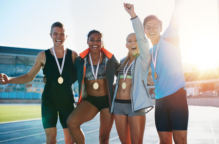 Portrait of ecstatic young athletes together with medals. Group of runners standing together smiling with their hands raised in excitement on racetrack on a bright sunny day. Imagens