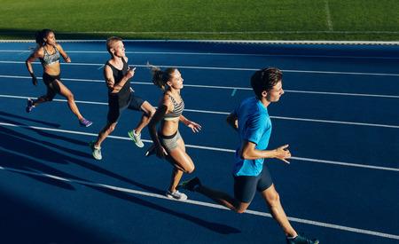Groep van multiraciale atleten oefenen draaien op circuit. Mannelijke en vrouwelijke atleten tijdens hardlopen sessie op atletiek stadion. Stockfoto