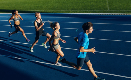 Group of multiracial athletes practicing running on racetrack. Male and female athletes during running session at athletics stadium.