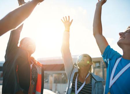 Skupina mladých sportovců slaví úspěch, když stál v hloučku. Úspěšné tým sportovců jásající vítězství. Reklamní fotografie