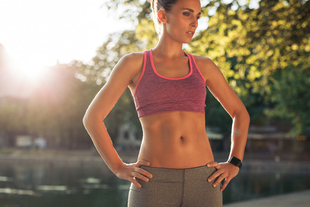 hand on hip: Woman taking break after sports training. She is standing with her hands on hips looking down on a summer day. Female athlete in wearing a smartwatch. Stock Photo