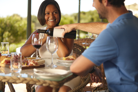 tomando vino: Mujer joven feliz sentado en la mesa con el hombre que vierte un vaso de vino tinto en el restaurante bodega. Foto de archivo