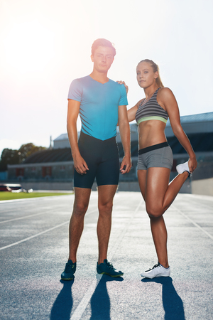 running track: Full length shot of young man and woman standing on athletics race track on a bright sunny day. Fit athletes on running track stretching before a run. Stock Photo