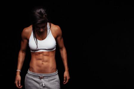 attitude: Imagen de la mujer de la aptitud en ropa deportiva mirando hacia abajo. Modelo de mujer joven con cuerpo musculoso. Estudio de tiro horizontal con espacio de copia en fondo negro. Foto de archivo