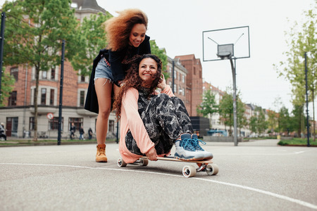 pushed: Happy young woman sitting on longboard being pushed by her friend along the road. Girls enjoying skating outdoors on city street. Stock Photo