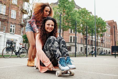 pushed: Outdoor shot of two happy young women playing with longboard. Young woman sitting on longboard being pushed by her friend.