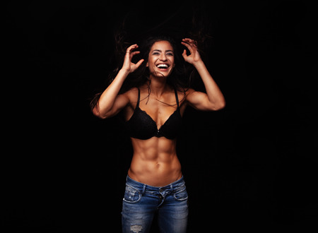 studio model: Portrait of cheerful young woman in bra and jeans. Muscular female model laughing on black background.