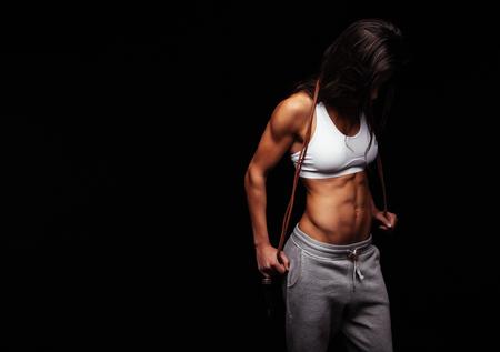 cuerpo femenino: Retrato de la mujer atleta celebraci�n saltar la cuerda mirando hacia abajo contra el fondo negro. Mujer con la presentaci�n del cuerpo musculoso. Salud y concepto de fitness.
