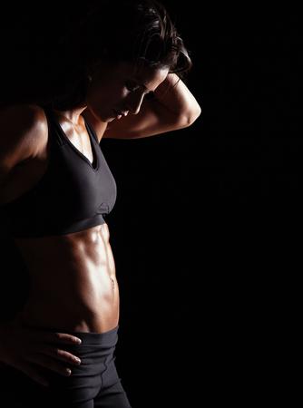 cuerpo femenino: Colocar la mujer con su mano en las caderas. Mujer con cuerpo musculoso sobre fondo negro. Foto de archivo
