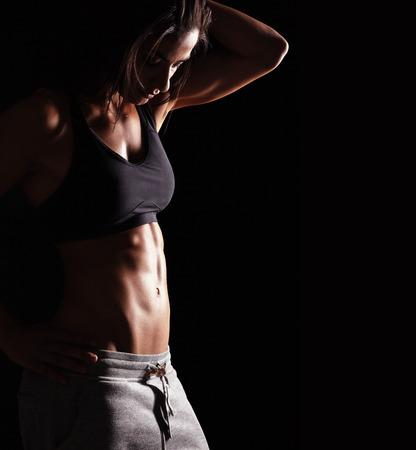 Imagen de la mujer de la aptitud en ropa deportiva mirando hacia abajo. Modelo de mujer joven con cuerpo musculoso. Estudio de tiro horizontal con espacio de copia en fondo negro. Foto de archivo