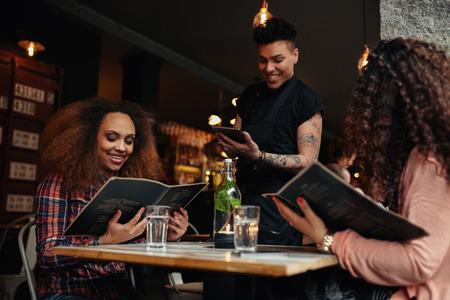レストランでメニューを保持するテーブルに座っている若い女性。選抜きのカフェで若い女の子と中にデジタル タブレットを待って立って、彼らの