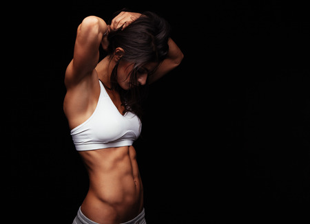 Studio ritratto di giovane donna di misura sta preparando per l'esercizio su sfondo nero. Giovane donna sportiva legando i capelli prima dell'allenamento. Archivio Fotografico - 45883757