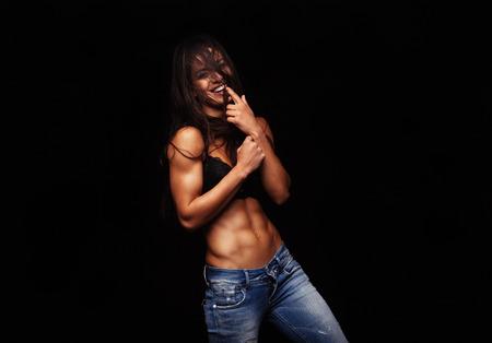 lenceria: Retrato de mujer joven feliz de pie contra el fondo negro. Modelo femenino posando en sujetador y pantalones vaqueros. Mujer divertida que muerde su dedo.