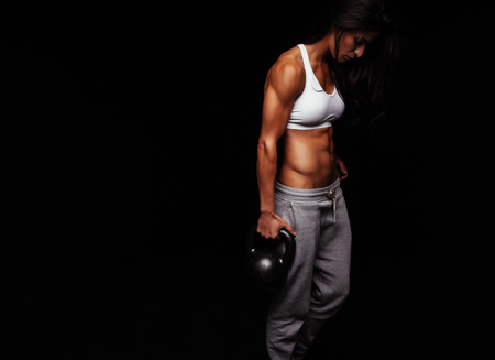 crossfit: Muscular woman doing crossfit exercise. Tough fitness female model with kettle bell on black background.