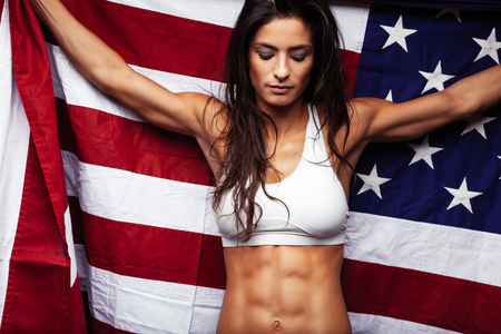 sports bar: Portrait of muscular female holding American Flag. Fit young woman wearing sports bar holding United States of American flag with her eyes closed. Stock Photo