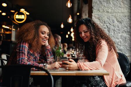 tabla de surf: Las mujeres j�venes sentados en el caf� y el uso de tel�fono. Amigos que se sientan en un restaurante con una mujer que muestra algo interesante a su amiga.