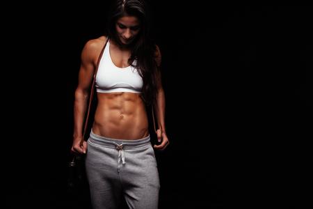 Portrait de jeune femme musculaire avec une corde à sauter. Female bodybuilder avec corde à sauter regardant vers le bas. Banque d'images - 45883768