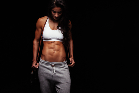 Portrait des muskulösen jungen Frau mit einem Seil springen. Bodybuilderin mit Springseil nach unten.