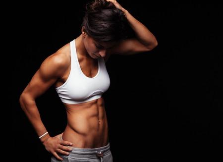 Mujer joven en blanco deportivo lencería de pie sobre fondo negro mirando hacia abajo. Modelo femenino de fitness con el torso musculoso mirando hacia abajo.