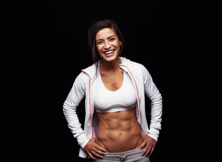 Gelukkig jonge vrouw in de sport kleding staan met de handen op de heupen lachend. Gespierde fitness model op zwarte achtergrond. Stockfoto