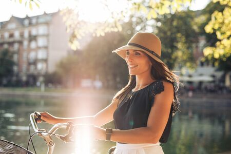 Portrait of happy young woman at the city park walking along a pond with her bicycle. European female model wearing hat looking away smiling. Sun flare effect. Banco de Imagens
