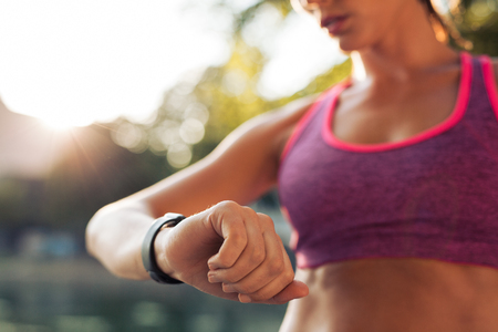 sports training: Young fitness woman looking at her smart watch while taking a break from sports training. Sportswoman checking pulse on fitness smart watch device. Stock Photo