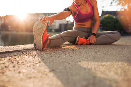 training shoes: Cropped shot of female runner stretching legs before doing her summer workout. Woman warming up before outdoor workout with sun flare. Stock Photo