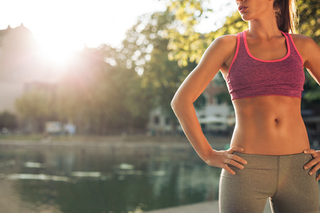 Cropped shot of fit young woman in sportswear standing with her hands on hips outdoors. Female runner ready for a run with sun flare. Stock Photo