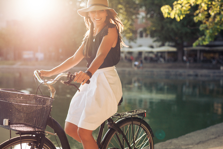 happy woman: Portrait of happy young female cycling by a pond. Woman wearing a hat on a summer day riding her bicycle at city park. Stock Photo