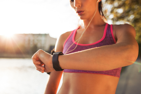 sportwoman: Young fitness woman looking at her smart watch while taking a break from outdoor workout. Sportwoman checking pulse on fitness smart watch device. Stock Photo
