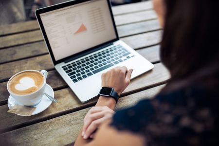 outdoor cafe: Female hand wearing a smartwatch sitting at a table with laptop and cup of coffee. Woman working on laptop at cafe.