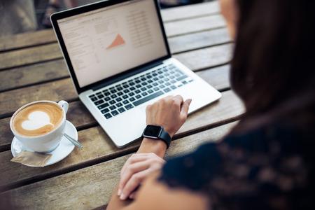 Mão fêmea que desgasta um smartwatch sentado a uma mesa com computador portátil e chávena de café. Mulher que trabalha no portátil no café.