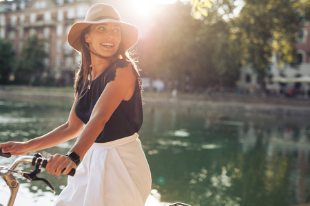 Portrait of happy young woman riding bicycle by a pond. Woman wearing a hat on a summer day looking over her shoulder.