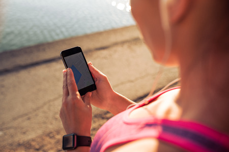 PULSE: Close up shot of woman reading a text message on her mobile phone. Sports woman using smart phone while taking a break from outdoor workout.