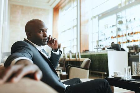 gerente: Hombre de negocios africano hablando por tel�fono m�vil mientras se espera en un pasillo del hotel. Ejecutivo de negocios joven que usa el tel�fono celular mientras se espera en el sal�n. Foto de archivo