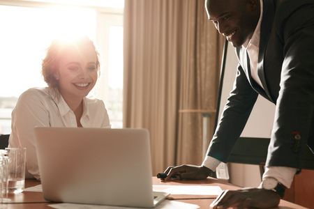 young conference: Portrait of happy young business team working together on laptop. Businessman and businesswoman meeting in conference room. Stock Photo